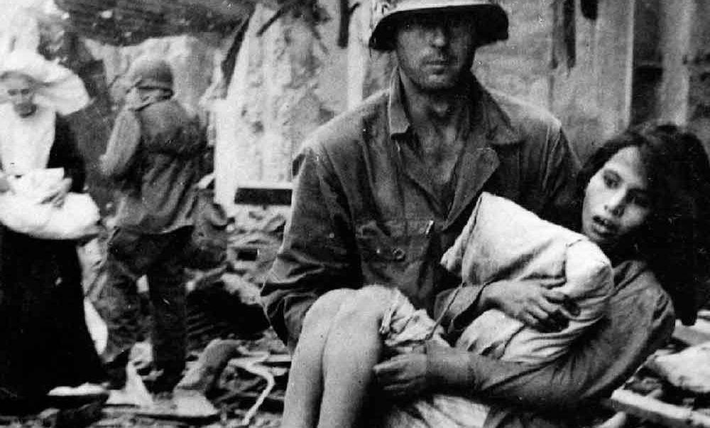 Amerykański żołnierz z ranną filipińską dziewczynką.