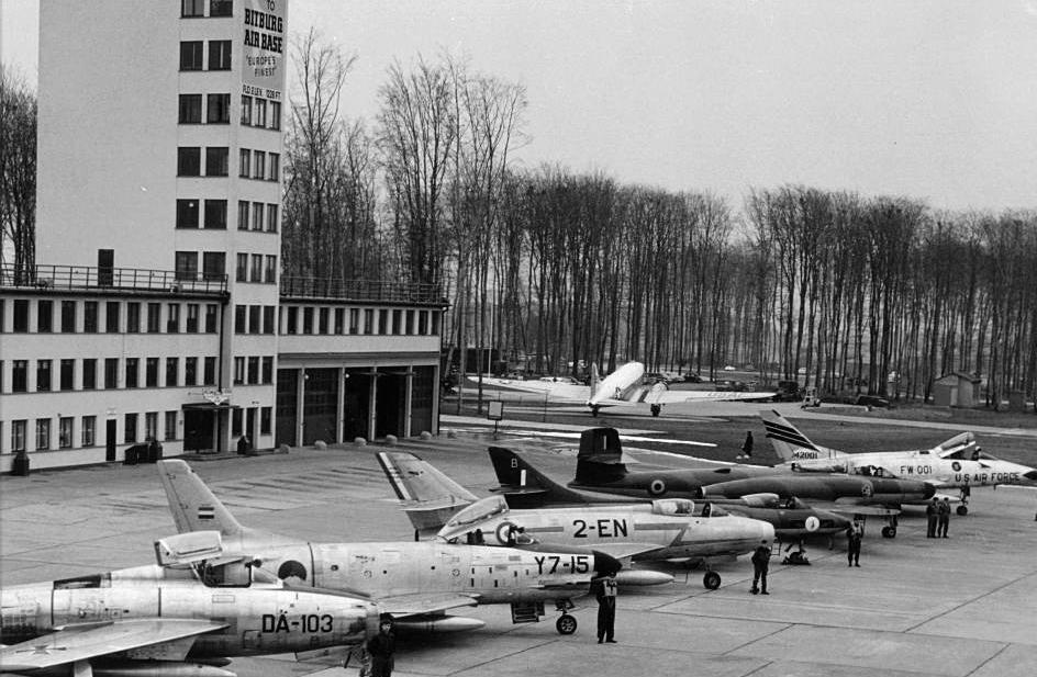 Belgijski CF-100 Canuck w towarzystwie myśliwców z innych państw NATO-wskich w zachodnioniemieckiej bazie lotniczej Bitburg (land Nadrenia-Palatynat) w 1959 roku. Na zdjęciu kolejno: F-84F Thunderstreak z Luftwaffe, holenderski F-86K Sabre, francuski Dassault Mystère IVA, brytyjski Hawker Hunter, CF-100 i amerykański F-100C Super Sabre. W tle C-47 Skytrain; fot. Gary Schulz, USAF