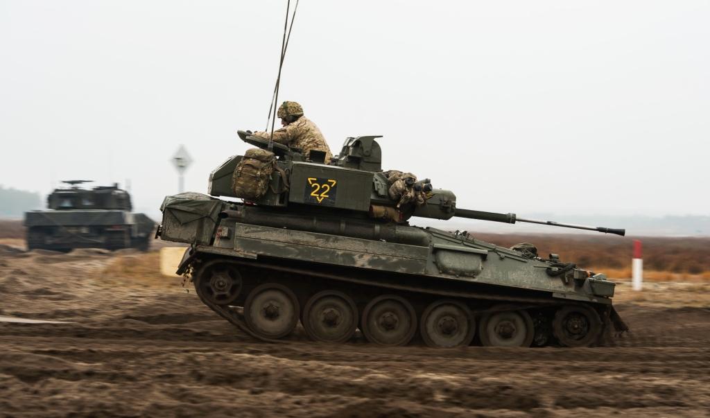 Lekki czołg rozpoznawczy Scimitar pędzi, ile sił w gąsienicach. W tle polski Leopard 2 (fot. SSgt Mark Nesbit RLC (Phot), © MOD / Crown Copyright)
