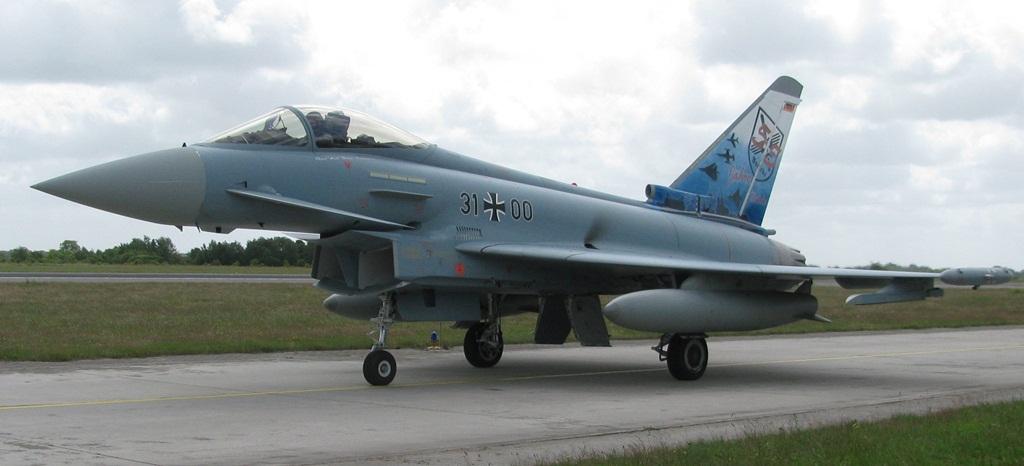 """Także Eurofighter 31+00 ma obie strony statecznika pomalowane w różny sposób. Z lewej widzimy malowanie z okazji pięćdziesięciopięciolecia 31. Skrzydła Lotnictwa Taktycznego """"Boelcke"""" – na niebieskim tle ze słynnymi budynkami Kolonii umieszczono sylwetki samolotów używanych przez to skrzydło w przeszłości i obecnie. Są tam F-84, F-104, Tornado i Typhoon oraz godło jednostki.  (fot. Maciej Hypś, konflikty.pl)"""