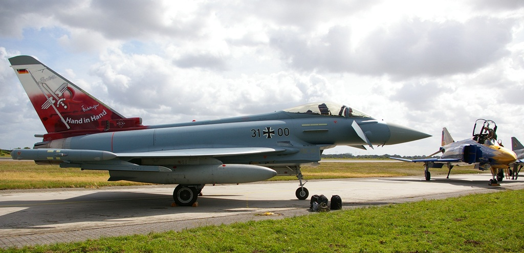 """Z prawej strony na czerwono-białym tle uzupełnionym o wizerunek linii brzegowej wschodniej Fryzji znalazło się hasło """"Hand in Hand"""" (ręka w rękę) oraz godła 31. Skrzydła """"Boelcke"""" i 71. Skrzydła """"Richthofen"""". Ma to związek z połączeniem obu jednostek, po tym jak z tej drugiej wycofano ze służby samoloty F-4 Phantom (widoczny w tle). (fot. Maciej Hypś, konflikty.pl)"""