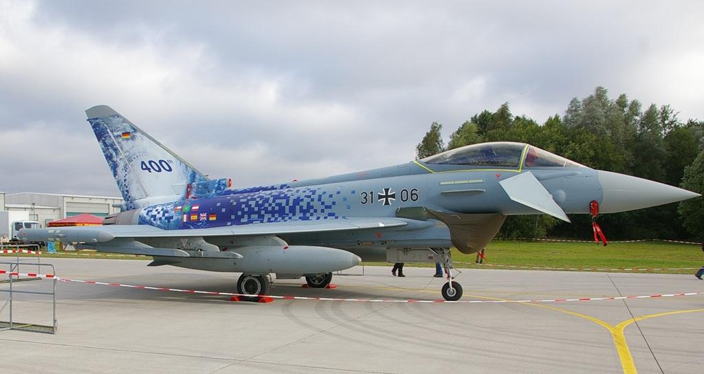 Na koniec jeszcze jeden Eurofighter o numerze 31+06. Pikselowe malowanie powstało z okazji wyprodukowania czterechsetnego egzemplarza tego myśliwca. Z tyłu kadłuba, pod statecznikiem pionowym, widzimy flagi państw, które zakupiły Eurofightera: Niemiec, Wielkiej Brytanii, Hiszpanii, Włoch, Austrii, Arabii Saudyjskiej i Omanu. Na samym stateczniku przedstawiono z kolei zdjęcie satelitarne tajfunu. Z powodu złych skojarzeń z pochodzącym z drugiej wojny światowej samolotem Hawker Typhoon, który siał zniszczenie wśród niemieckiej broni pancernej, w Niemczech używa się jednak głownie nazwy Eurofighter. (fot. Maciej Hypś, konflikty.pl)