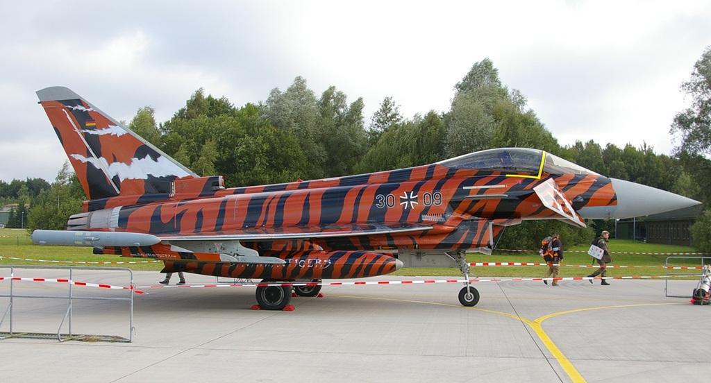 """Ten Eurofigher 30+09 pochodzi z 74. Skrzydła Myśliwskiego, w skład którego wchodzą 741. i 742. Eskadra – choć same nie mają w godłach tygrysa, skrzydło jako całość przejęło tradycje (a wraz z nią także """"ducha tygrysa"""") z rozwiązanej 321. Eskadry i jest członkiem przygotowawczym NATO Tiger Meet. Jest to jeden ze wspomnianych wyjątków, w których jednostka nie musi mieć tygrysa w godle. Zarazem jest to pierwszy w historii Eurofighter w całości pomalowany w tygrysie barwy. W czasie zlotu w 2014 roku otrzymał nagrodę za najlepsze malowanie. (fot. Maciej Hypś, konflikty.pl)"""