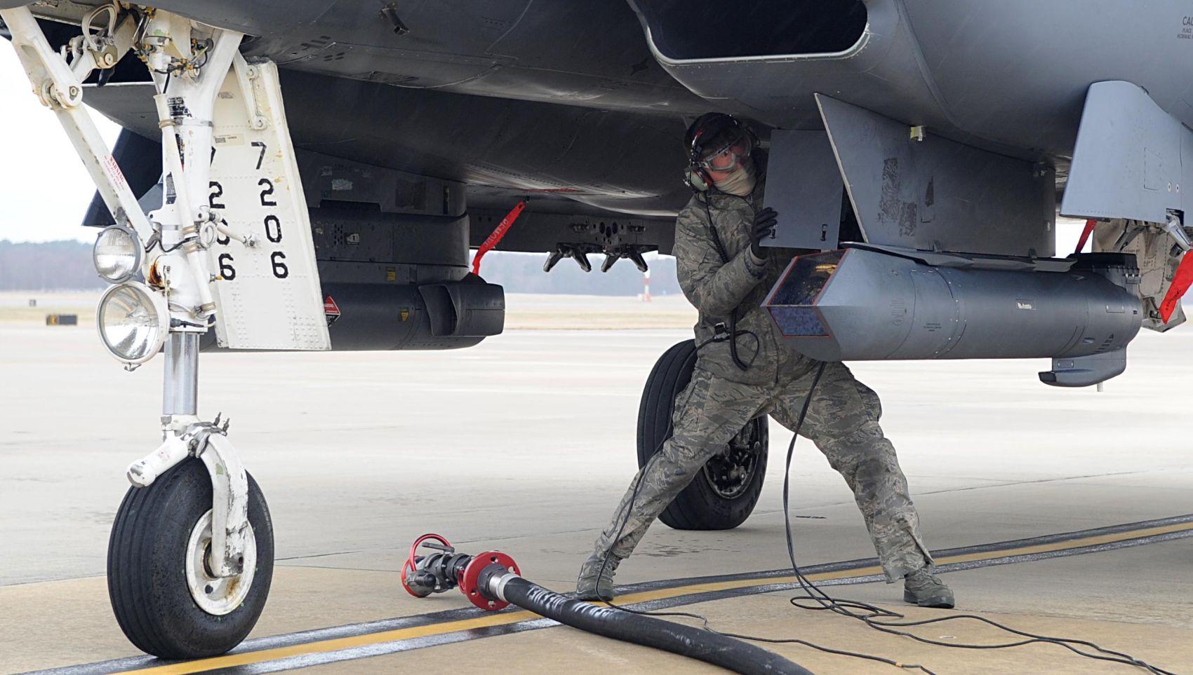Mechanik przygotowuje F-15E do tankowania z włączonym silnikiem (hot pit refueling); na pierwszym planie widoczny zasobnik celowniczy Sniper (fot. US Air Force / Senior Airman Ashley J. Thum)