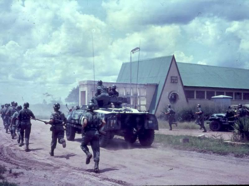 """Żołnierze ONZ wspierani przez zdobyczny pokatangijski samochód pancerny M8 Scout atakują pozycje Gendarmerie w Elizabethville podczas operacji """"Wielki Szlem"""" w końcu grudnia 1962 roku (fot. nieznany duński żołnierz ONZ, za pośrednictwem: Alfred Blume)"""